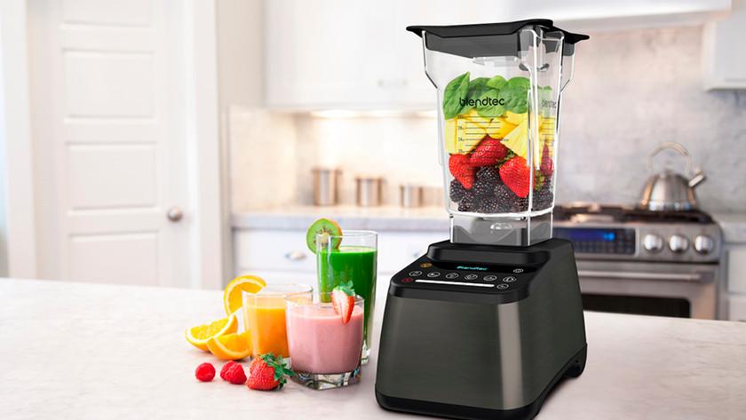 Blendtec-Mixer gefüllt mit Obst und Tassen mit Smoothies