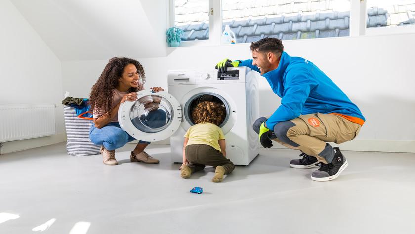 Lieferant mit Waschmaschine, Kunde und Kind