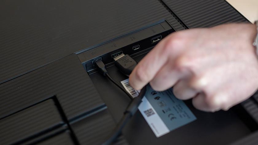 Mann schließt HDMI-Kabel an Monitor an