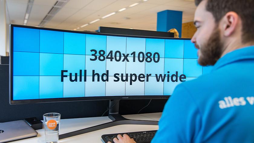 Mann arbeitet am UltraWide-Monitor und schaut sich die Auflösung an