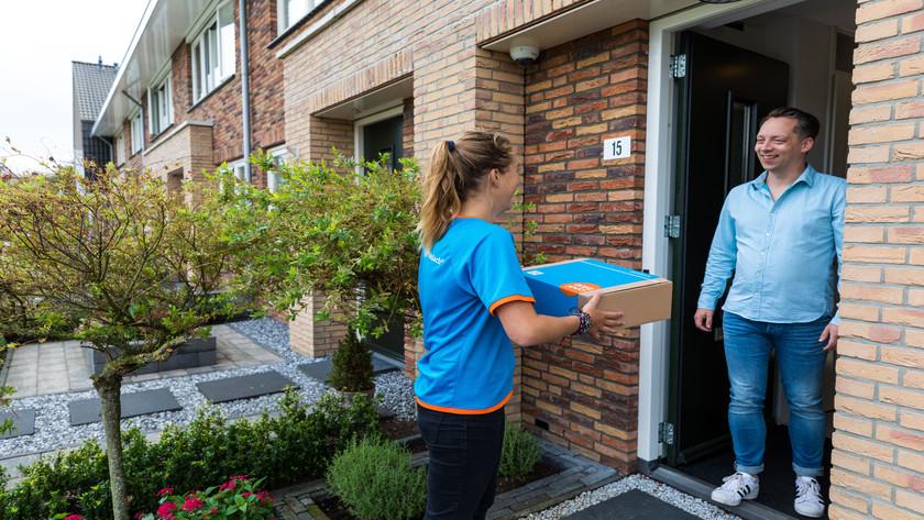 Lieferant an der Tür mit Paket und Kunde