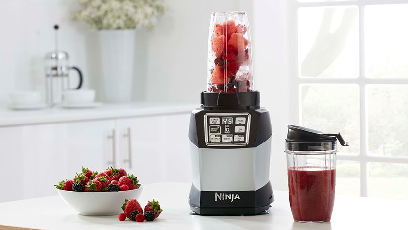 Ninja-Mixer und mit roten Früchten gefüllter Mixbecher