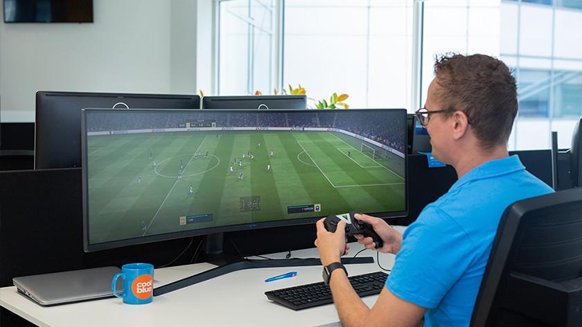 Mann spielt FIFA auf Ultrawide-Monitor für Konsolenspiele